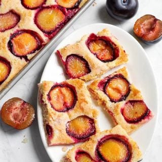 Fresh Plum Cake, also called Pflaumenkuchen and Zwetschgenkuchen (German Plum Cake) is a thin sheet cake baked with fresh plum slices on it. This Fresh Plum Cake recipe is simple, and not too sweet. A great way to use your fresh ripe plums! simplyhappyfoodie.com #freshplumcake #Pflaumenkuchen #Zwetschgenkuchen