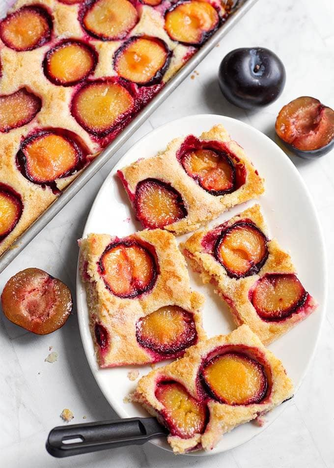 Fresh Plum Cake, also called Pflaumenkuchen and Zwetschgenkuchen (German Plum Cake) is a thin sheet cake baked with fresh plum slices on it. This Fresh Plum Cake recipe is simple, and not too sweet. A great way to use your fresh, ripe plums! simplyhappyfoodie.com #freshplumcake #Pflaumenkuchen #Zwetschgenkuchen