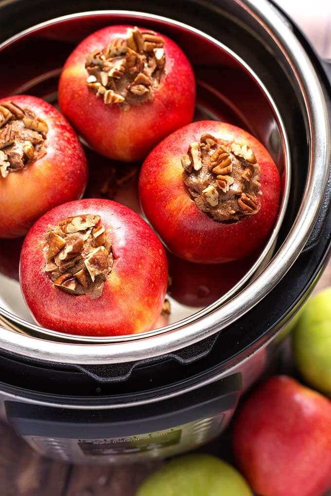 Instant Pot Baked Apples are a delicious sweet treat! These pressure cooker baked apples are flavored with a tasty cinnamon butter, and only take minutes to cook. We love how easy it is to make baked apples in the Instant Pot! simplyhappyfoodie.com #instantpotbakedapples #pressurecookerbakedapples #bakedapples
