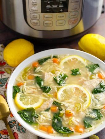 Lemon Chicken Orzo Soup in a white bowl in front of a pressure cooker is a light and delicious soup that you can make in minutes. This pressure cooker lemon chicken orzo soup is a healthy and simple Instant Pot chicken soup. simplyhappyfoodie.com #instantpotchickensoup #instantpotsoup #pressurecookerchickensoup