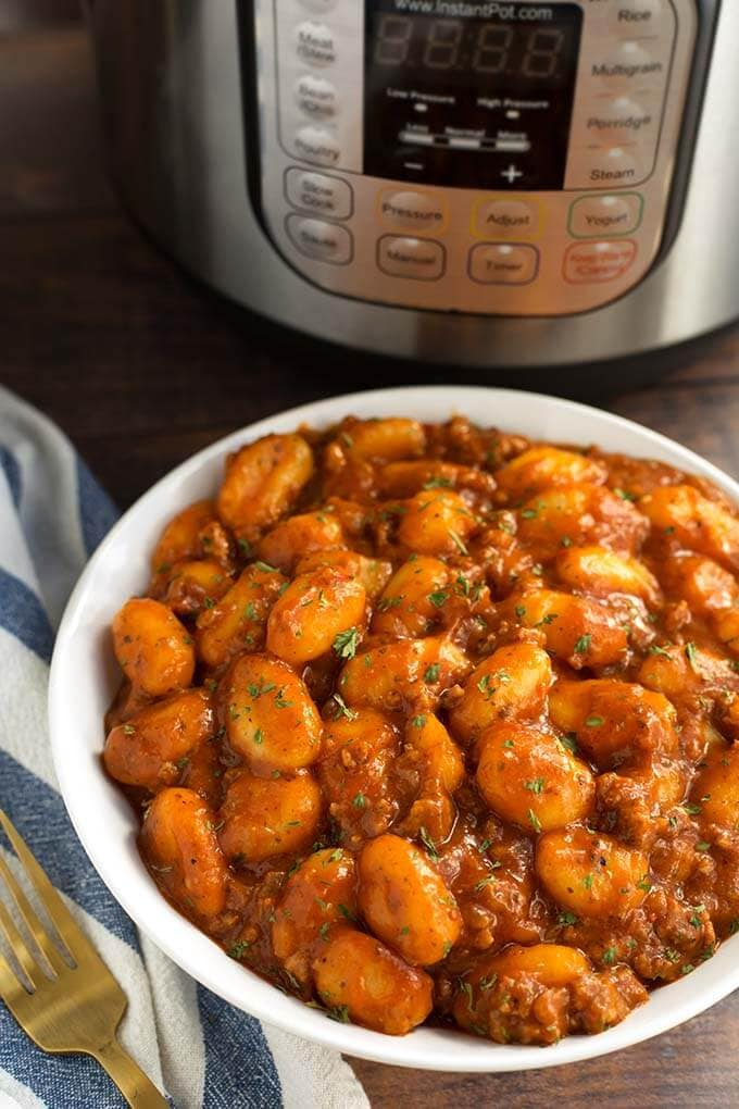 White bowl of Sausage Gnocchi in front of a pressure cooker