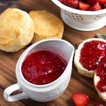 Instant Pot Strawberry Sauce is sweet and delicious on everything from ice cream and yogurt, to biscuits and pancakes! You can make this pressure cooker strawberry sauce quickly and easily from fresh or frozen strawberries. simplyhappyfoodie.com #instantpotstrawberrysauce #strawberrysyrup #pressurecookerstrawberrysyrup