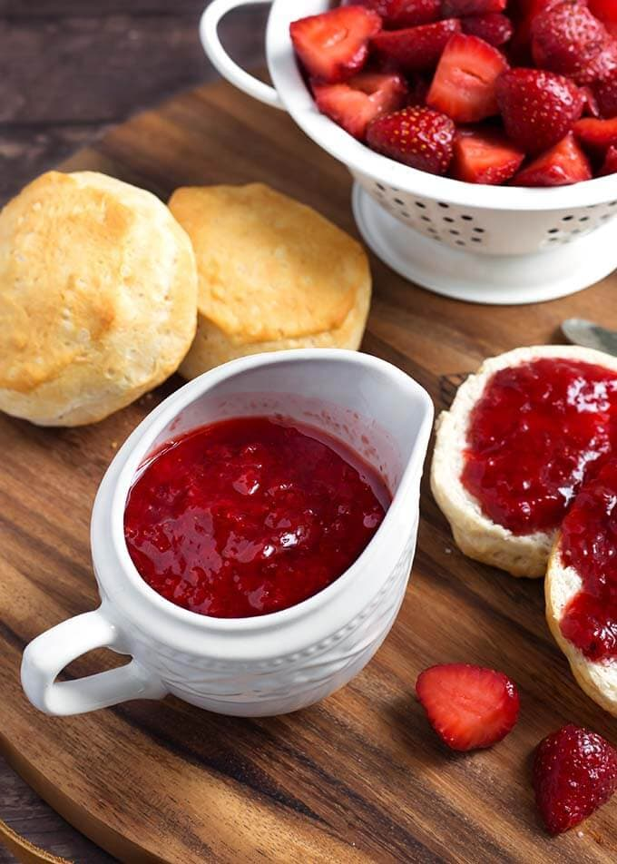 Strawberry Sauce in a small white pitcher next to biscuits with strawberry syrup spread on them next to a white colander full of halved strawberries