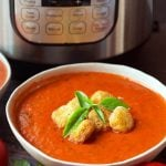 Instant Pot Fresh Tomato Basil Soup is the most delicious way to use up your summer bounty of garden fresh tomatoes and basil! We love the fresh, rich flavor of this pressure cooker tomato basil soup. Add some crispy croutons and you will have a healthy, tasty meal! You can roast your tomatoes and garlic together first for even more sweet tomato flavor in this Instant Pot tomato basil soup! simplyhappyfoodie.com #instantpottomatobasilsoup #instantpotfreshtomatosoup #instantpotsouprecipe #pressurecookertomatosoup