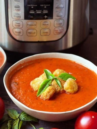 Fresh Tomato Basil Soup topped with croutons and fresh basil, in a white bowl