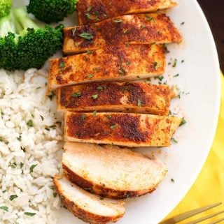 Sliced Baked Chicken Breast on a white plate with rice and broccoli