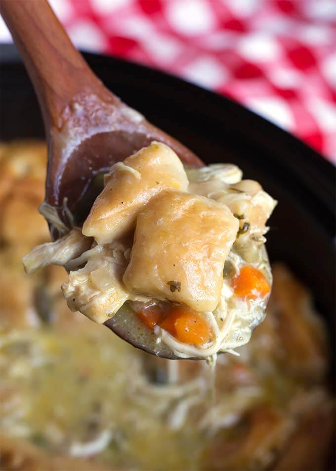 Closeup of a wooden spoon full of Chicken and Dumplings over the slow cooker