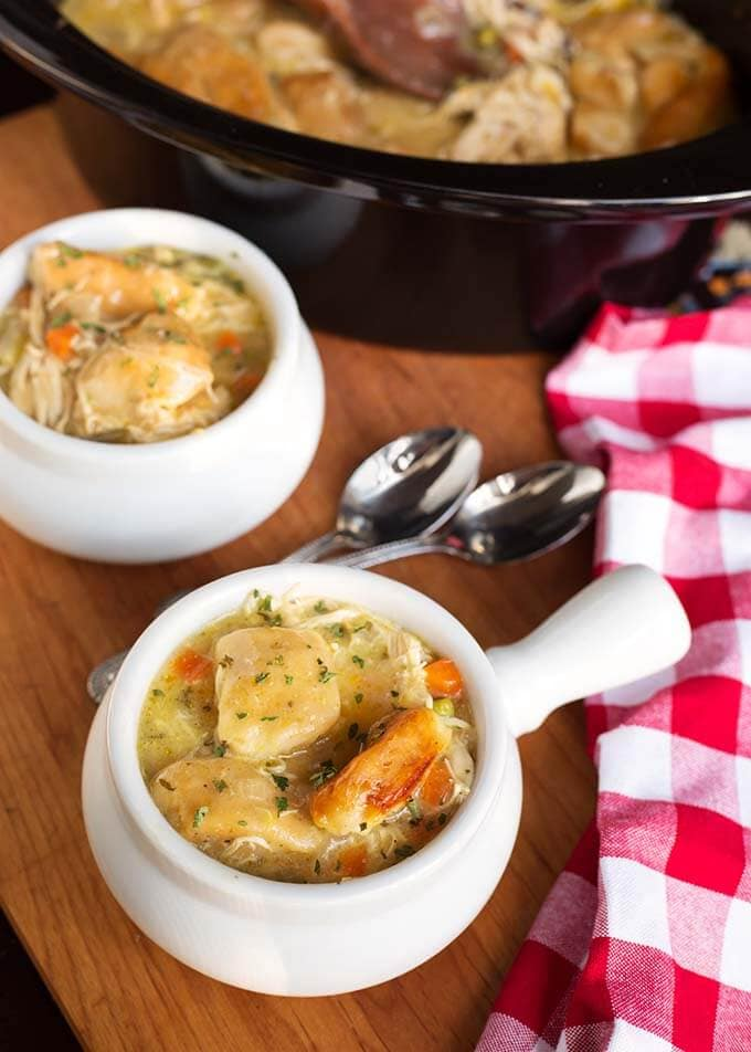 Two white bowls of Chicken and Dumplings next to a red gingham napkin and two spoons in front of a slow cooker
