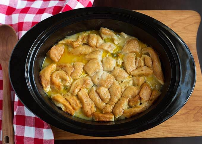 Top view of Chicken and Dumplings in a slow cooker next to a red gingham napkin