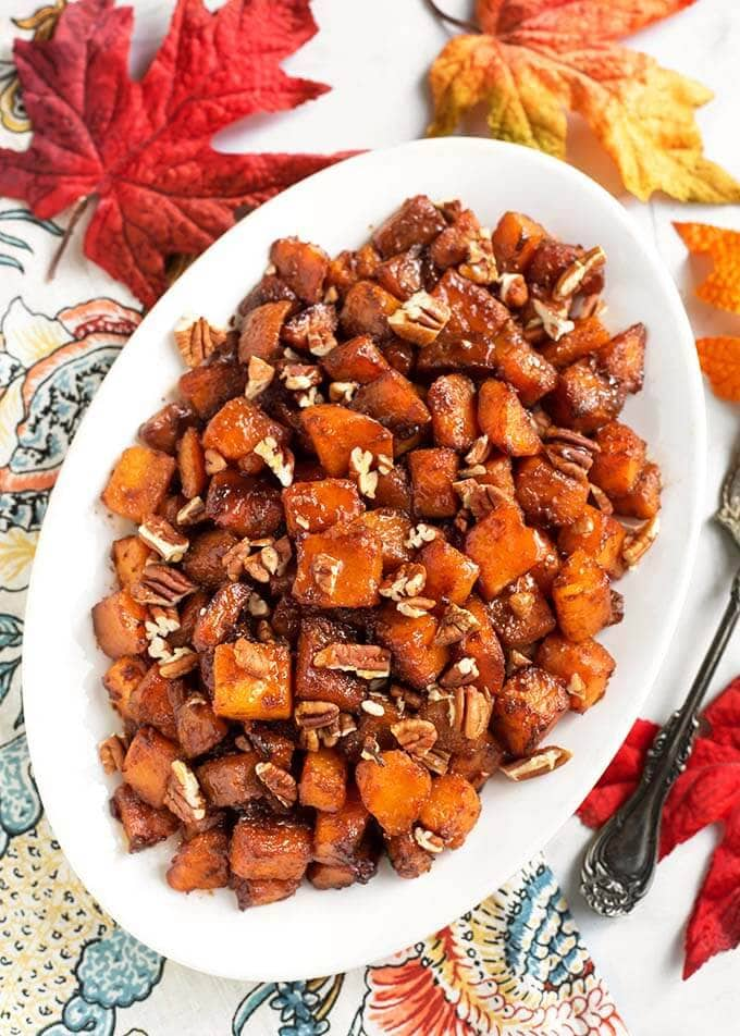 Cinnamon Roasted Butternut Squash is a delicious side dish recipe that is perfect for Thanksgiving, or any holiday. The warm spice of the cinnamon and caramelized brown sugar transforms the butternut squash into a special vegetable side dish! simplyhappyfoodie.com #butternutsquash #thanksgivingsidedish