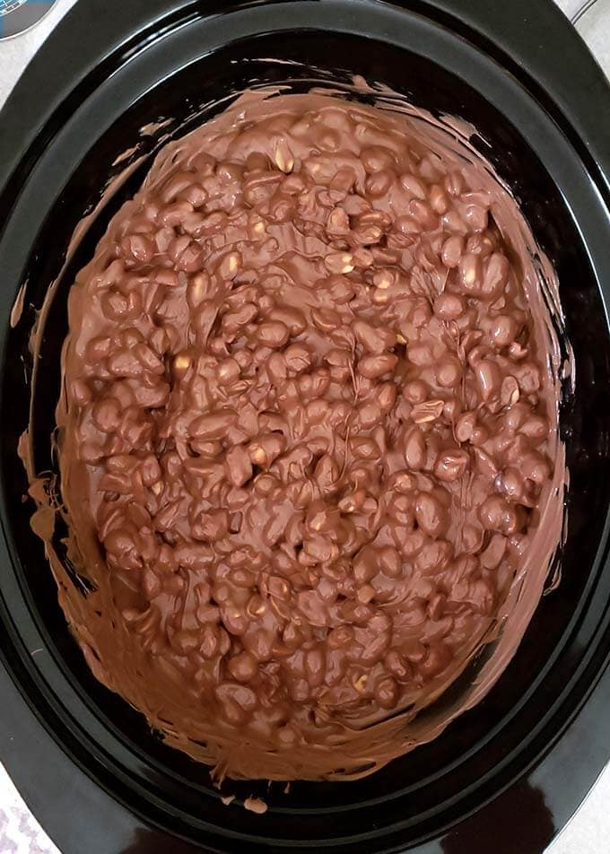 Crock Pot Chocolate Peanut Clusters candy is a sweet and lightly salty delight! This easy candy recipe combines different types of chocolate to make the best chocolate peanut clusters! Make this chocolate peanut clusters candy in your slow cooker for the easiest chocolate candy recipe ever! simplyhappyfoodie.com #chocolatepeanutclusters #crockpotcandy