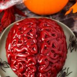 Halloween Jello Brain on a green plate with plastic black spiders in front of a small pumpkin