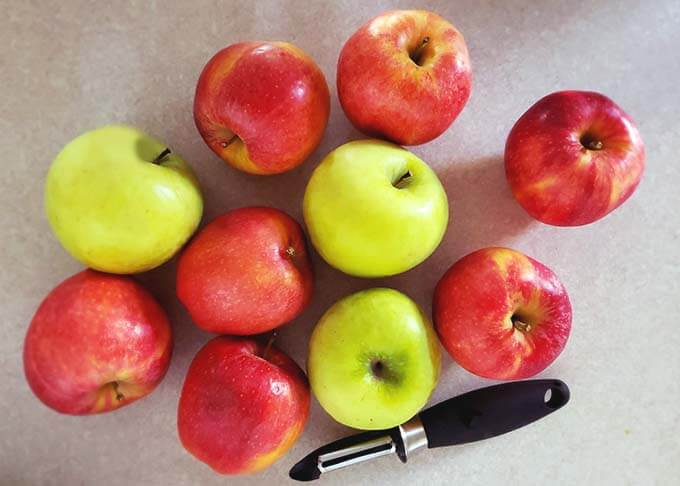 Several red and green apples next to a vegetable peeler