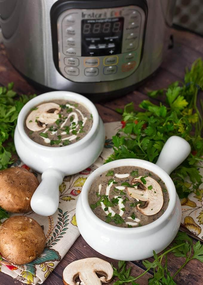 Two white handled bowls of Mushroom Soup next to parsley and mushrooms in front of a pressure cooker