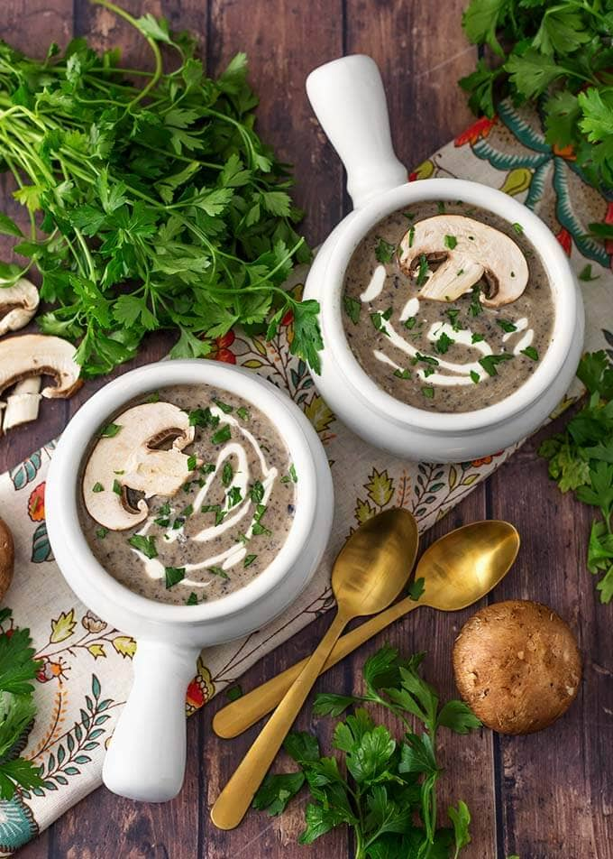 Top view of two white handled bowls of Mushroom Soup recipe next to two golden spoons,parsley and mushrooms