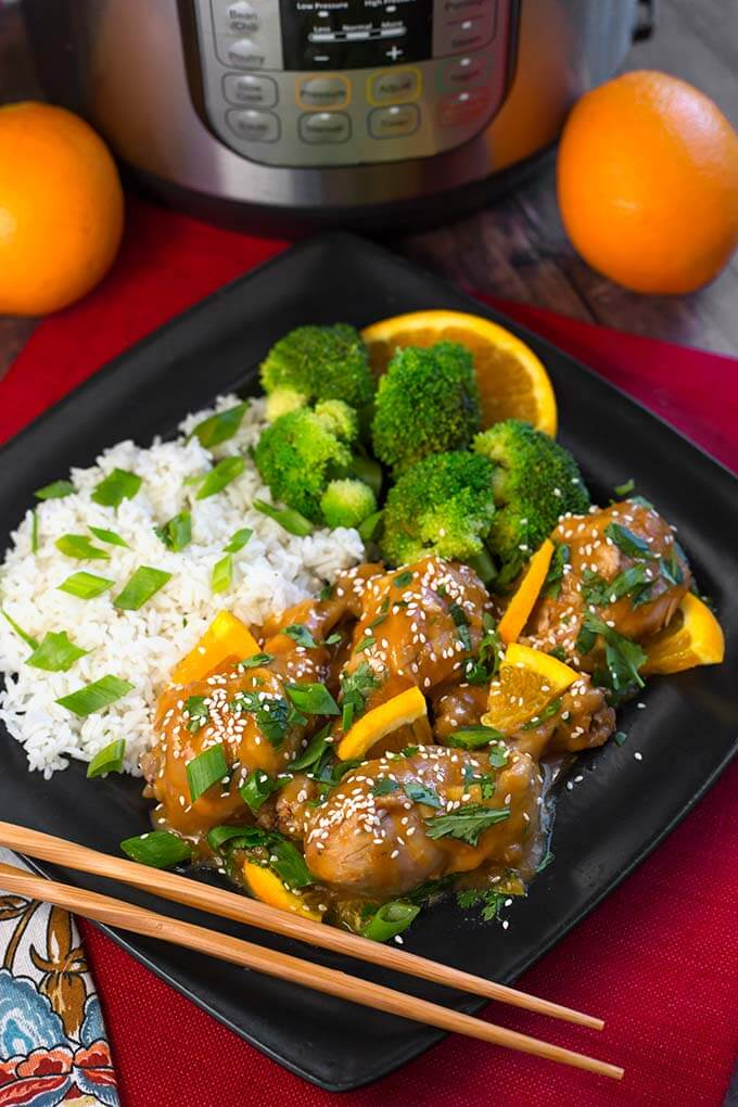 Orange Chicken Legs with rice, broccoli, and an orange slice on a square black plate with chopsticks, in front of a pressure cooker