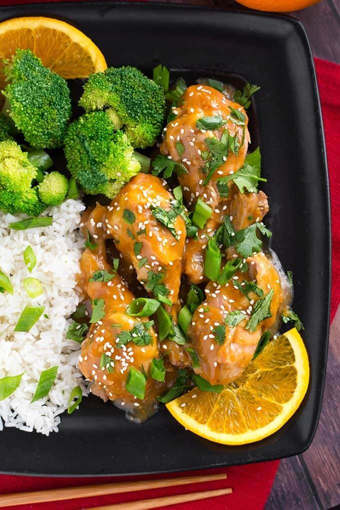 Orange Chicken Legs with rice, broccoli, and an orange slice on a square black plate