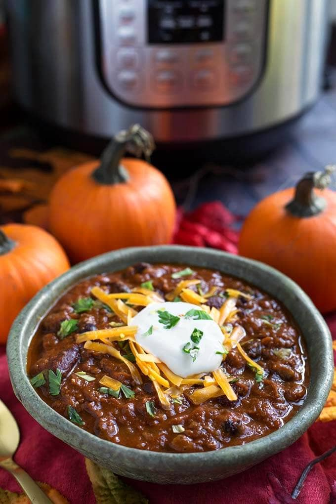 Pumpkin Chili topped with shredded cheese and sour cream in a turquoise bowl in front of a pressure cooker