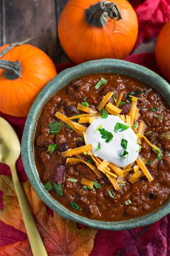 Pumpkin Chili topped with shredded cheese and sour cream in a turquoise bowl