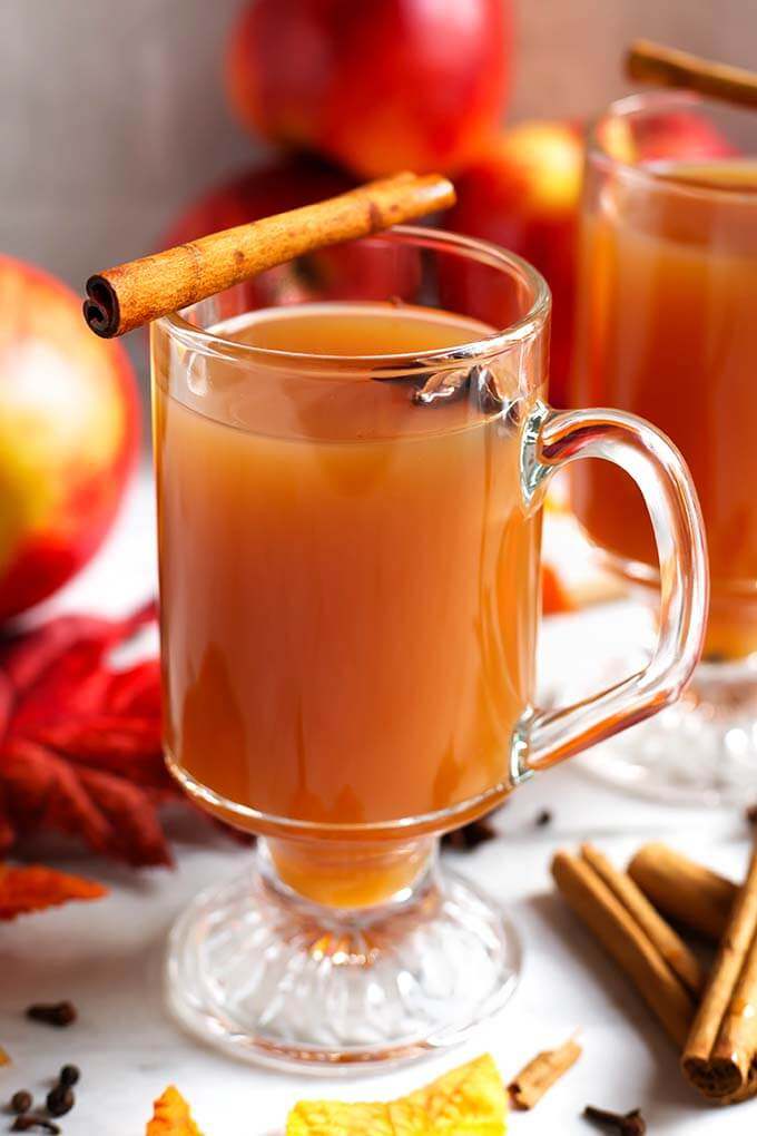 Spiced Apple Hot Toddy in a glass topped with a cinnamon stick