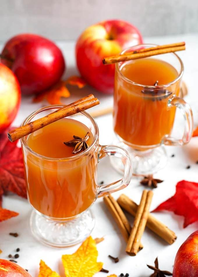 Two Spiced Apple Hot Toddy in glasses topped with cinnamon sticks and anise seeds, surrounded by cinnamon sticks, whole cloves and anise seeds as well as apples and fall leaves