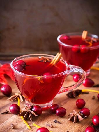 Two glasses of Spiced Cranberry Hot Toddy on a wooden board