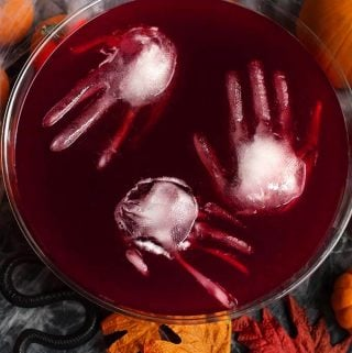 Spooky Halloween Party Punch is a fun drink to serve your guests at your Halloween Party. Scary ice sculptures make a chilling addition to this bloody delicious beverage. Halloween punch by simplyhappyfoodie.com #halloweenpartypunch #halloween