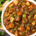 Classic Beef Stew in a white bowl on a wooden board next to fresh parsley
