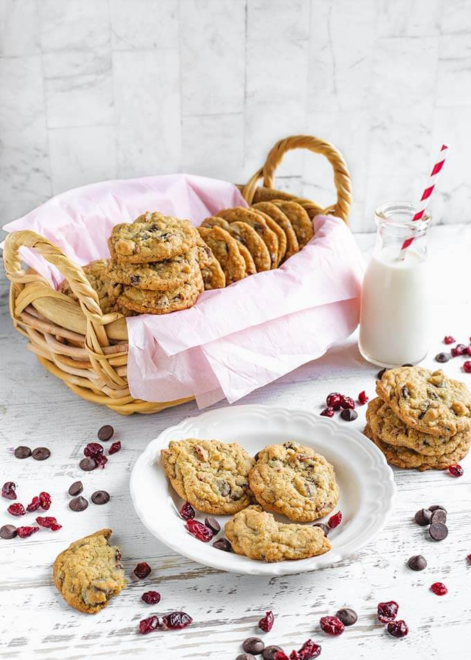 Three Cranberry Dark Chocolate Cookies on a white plate in front of a oblong basket lined with a pink napkin with several cookies inside as well as a glass of milk with a red and white stripped straw with other cookies stacked all on a white wood background