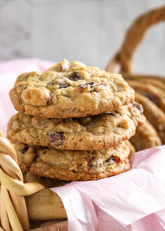 Closeup of three Cranberry Dark Chocolate Cookies stacked on a basket lined with a pink napkin
