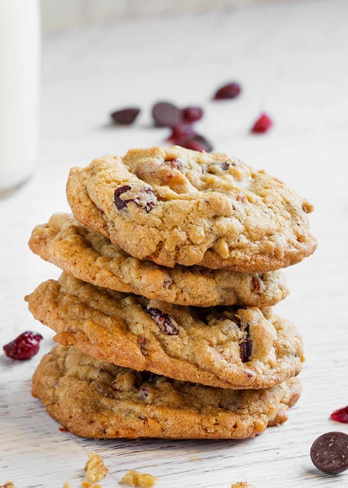 Four Cranberry Dark Chocolate Cookies stacked on a white wood background