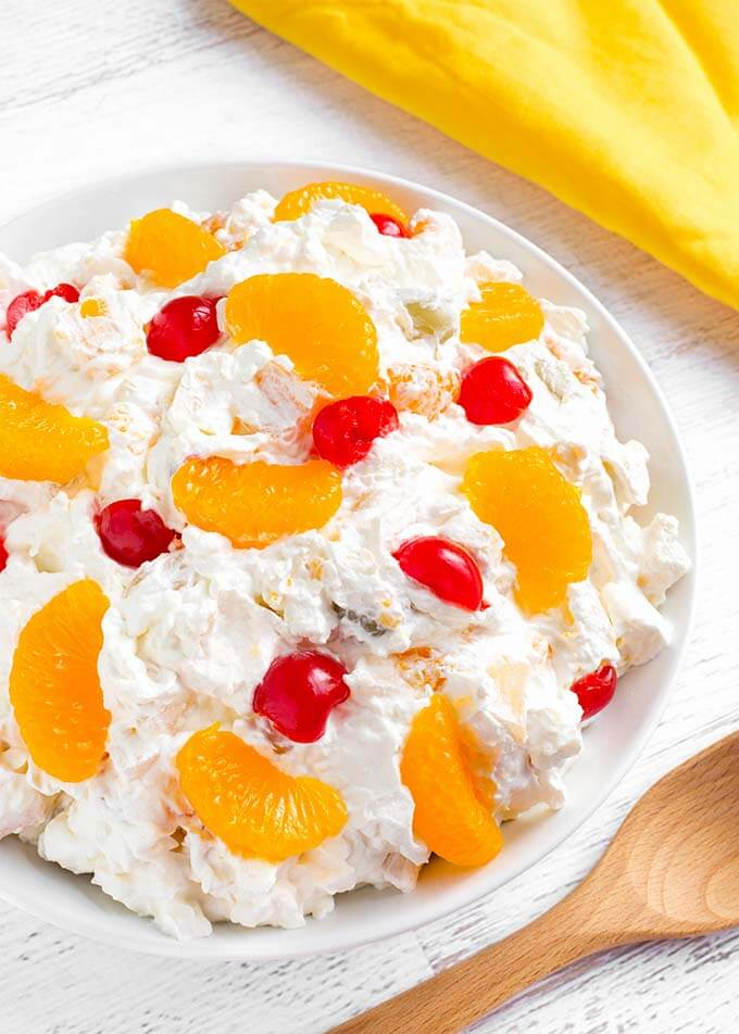 Creamy Cheesecake Fruit Salad is deliciously creamy, and not too sweet. This is a very easy fruit salad to make, with fruit cocktail and other tasty ingredients! This is our Holiday and special occasion fruit salad recipe. simplyhappyfoodie.com #fruitsaladrecipe #cheesecakefruitsalad