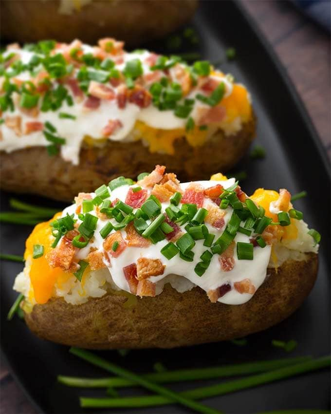 Make a yummy, fluffy Instant Pot Baked Potatoes, or 4, or even 8 in your electric pressure cooker! Making pressure cooker baked potatoes is so easy, and the resulting baked potato is much better than a microwaved potato! Give these pressure cooked baked potatoes a try! simplyhappyfoodie.com #instantpotbakedpotatoes #pressurecookerbakedpotato