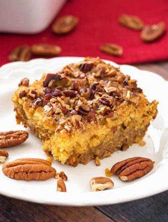 Slice of Pumpkin Pie Dump Cake on a white plate with pecan halves