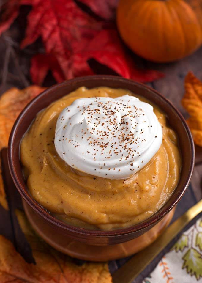 Quick Pumpkin Pie Pudding topped with a dollop of whipped cream in a wooden bolwon wooden coasters in front of red and orange leaves and pumpkins