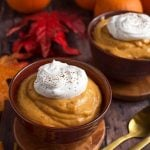 Quick Pumpkin Pie Pudding topped with a dollop of whipped cream on wooden coasters in front of red and orange leaves and pumpkins