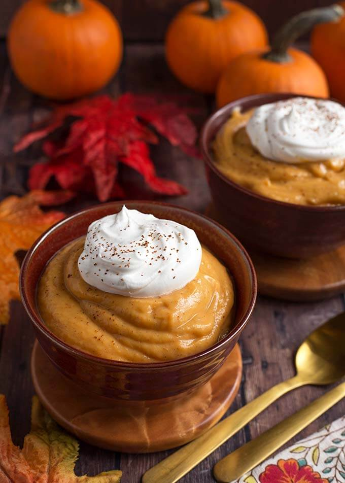 two wooden bowls of Quick Pumpkin Pie Pudding topped with a dollop of whipped cream on wooden coasters in front of red and orange leaves and pumpkins