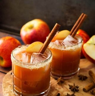 Two Apple Butter Old Fashioned Cocktails in glasses with salted rim on a wooden board with spices and apples