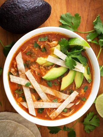 Chicken Tortilla Soup in a white bowl topped with tortilla strips, sliced avocados, and cilantro