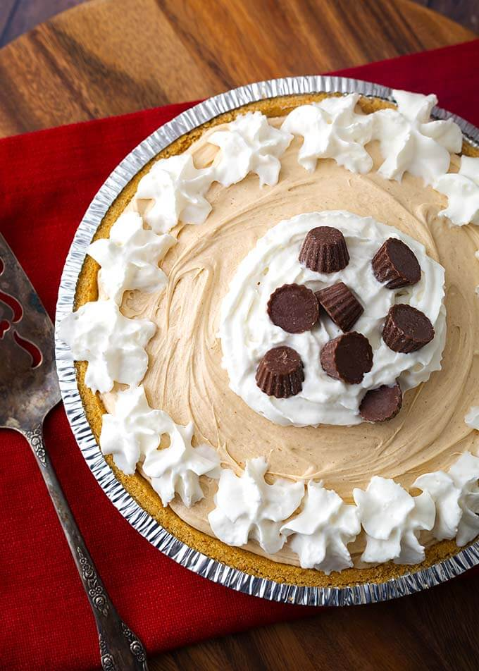 No Bake Peanut Butter Pie topped with whipped cream and chocolate candies in a disposable pie tin next to a silver serving spoon all on a wooden board