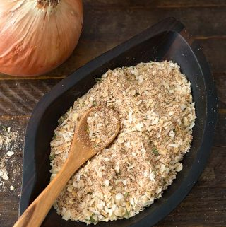 Homemade Onion Soup Mix in a dark wooden leaf-shaped bowl with a wooden spoon