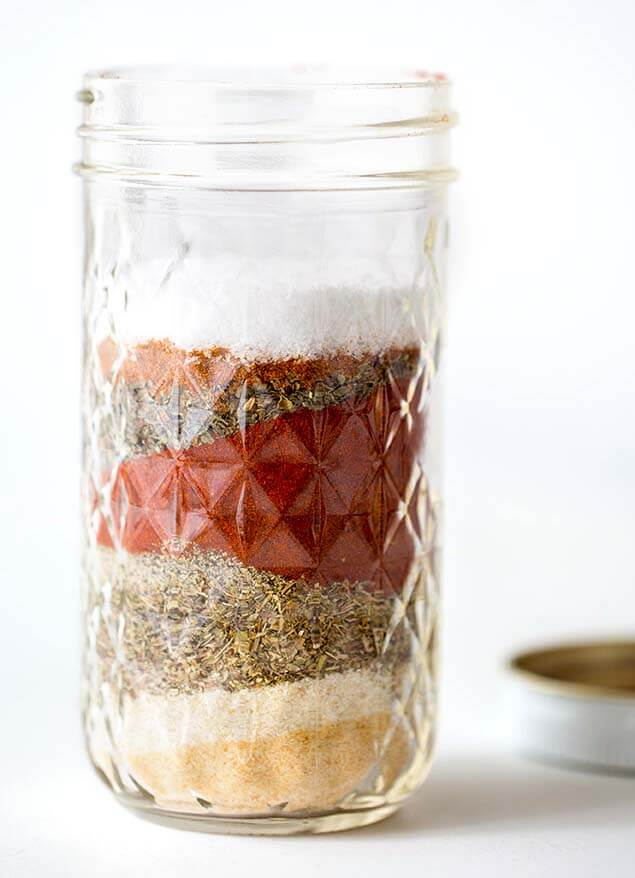 Small canning jar with layered Homemade Cajun Spice Blend