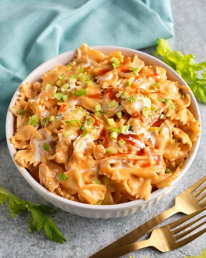 Buffalo Chicken Pasta in a white bowl next to two gold forks