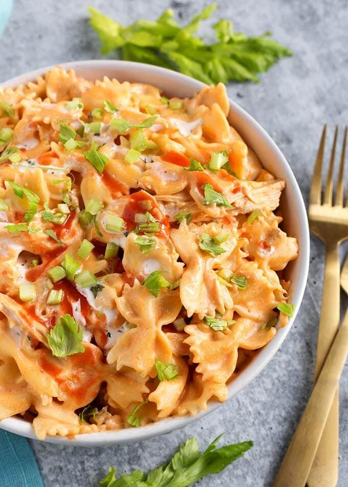 Instant Pot Buffalo Chicken Pasta is zesty, rich, and delicious! The flavor is like that of Buffalo Chicken Wings, only in a bowl of creamy, cheesy pasta! This pressure cooker Buffalo Chicken Pasta is easy to make, and is great for a weeknight meal, or for a Game Day party! simplyhappyfoodie.com #instantpotbuffalochickenpasta #pressurecookerbuffalochickenpasta