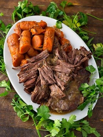 Pot Roast and carrots on a white oblong platter surrounded by fresh parsley