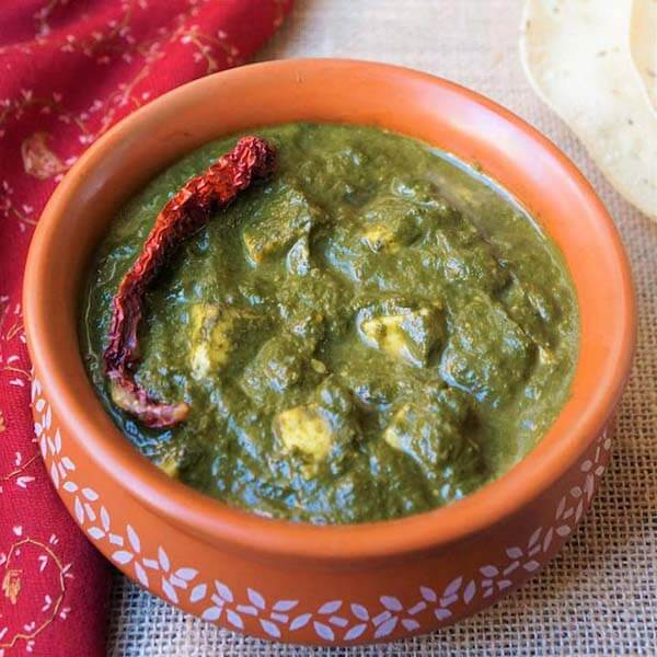 Palak Paneer in a orange bowl with white pattern
