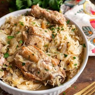 Crock Pot Pork and Sauerkraut is a tasty German recipe. This slow cooker pork and sauerkraut recipe has fall apart pork ribs and tangy sauerkraut. Good family meal! simplyhappyfoodie.com #slowcookerporksauerkraut #crockpotporksauerkraut