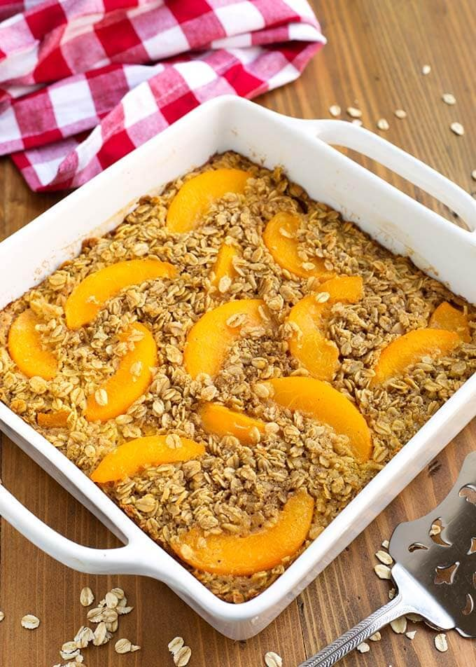 Peach Baked Oatmeal in a white square baking dish next to a red gingham napkin