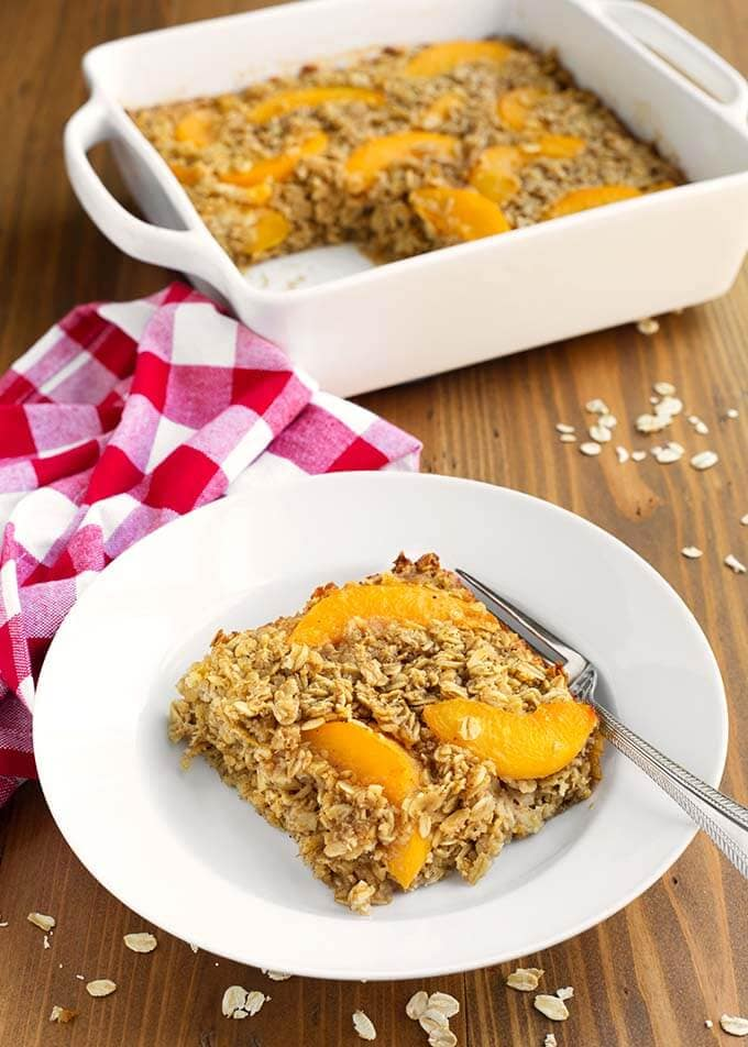 Slice of Easy Peach Baked Oatmeal with a fork on a white plate in front of white baking dish with rest of peach baked oatmeal