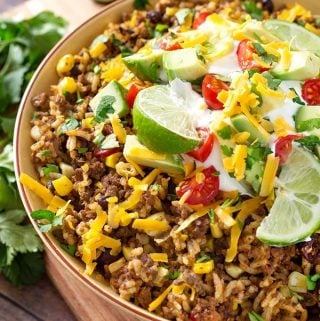 Instant Pot Beef Taco Bowls are an easy to make Instant Pot dump and start recipe. Delicious taco flavor, ground beef, beans, corn, and rice make this a one-pot meal. This pressure cooker beef taco bowl is perfect for meal prep, and is a healthy lunch or dinner. simplyhappyfoodie.com #instantpottacobowl #instantpotbeeftacobowl #pressurecookertacobowl